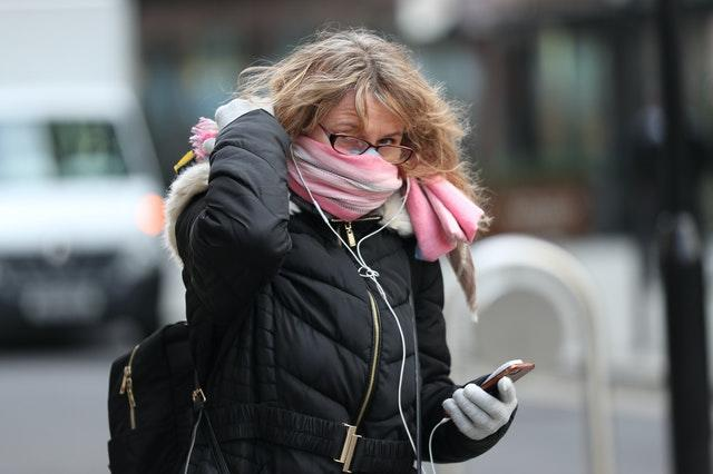 A woman with a scarf covering her mouth an nose
