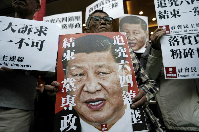 "Pro-democracy activists hold up placards of Chinese President Xi Jinping at a ferry terminal in Hong Kong, Wednesday, Dec. 18, 2019. A ferry company barred a Hong Kong activist ""Long Hair"", whose real name is Leung Kwok-hung, from boarding a boat Wednesday to Macao, where Chinese President Xi Jinping is slated to arrive for the 20th anniversary of Macau's return to China, The placards read ""Vindicate June 4th"" and ""Put an end to one-party Dictatorship"". (AP Photo/Kin Cheung)"