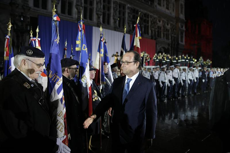 French President Francois Hollande salutes veterans in front of Paris' town hall on August 25, 2014, during a ceremony to commemorate the 70th anniversary of the liberation of Paris from Nazi occupation during World War II (AFP Photo/Joel Saget )