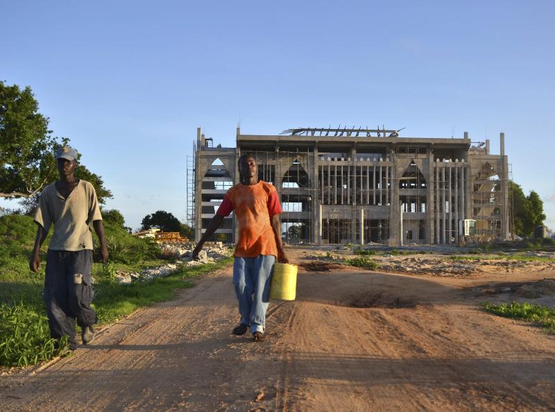 Workers walk in front of the construction site of the new building that will house the administrative headquarters for the Kenya Ports Authority, for a new port project along the Kenyan coast, April 17, 2013. A mega-port project on the north Kenyan coast conceived in the 1970s may finally be gaining traction based on commercial oil finds in Uganda and Kenya, but needs more financing to compete with a Chinese-backed port in Tanzania and other rivals. Initial work has started on a mangrove coast near the ancient Arab trading post of Lamu that could in a few years be a bustling container port and crude terminal, creating an export hub for fast-growing east African states and their oil. But Kenya must shore up regional commitment for the $25.5 billion Lamu Port-South Sudan-Ethiopia Transport (LAPSSET) plan that by 2030 envisages a port, new roads, a railway and pipeline. Picture taken April 17, 2013. To match Analysis KENYA-PORT/ REUTERS/Anjali Nayar (KENYA - Tags: BUSINESS CONSTRUCTION MARITIME)