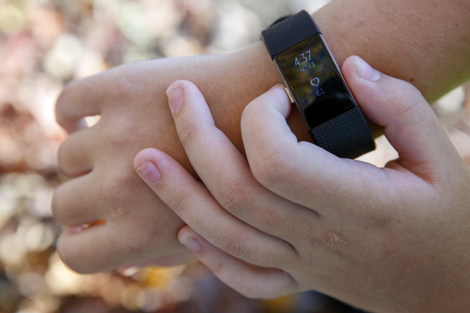 "Grace Brown, 14, adjusts her fitness tracker at the park where she does her jogging workouts for her ""online PE"" class, in Alexandria, Va., Friday, Nov. 1, 2019. Brown chose to take ""online PE,"" utilizing a fitness tracker, so that she could take a piano lab as an extra elective. (AP Photo/Jacquelyn Martin)"