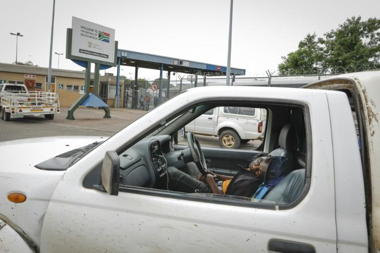 A man looking to cross the border sleeps inside his pick-up truck -- the coronavirus has complicated crossings which can take days