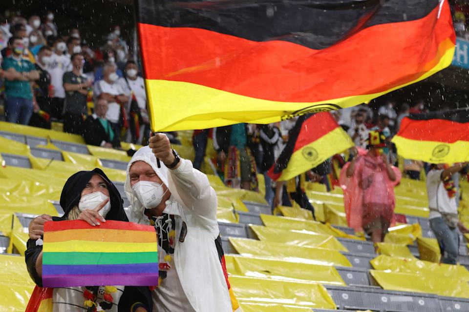 Germany fans, one holding a rainbow flag, cheer prior to the UEFA EURO 2020 Group F football match between Germany and Hungary at the Allianz Arena in Munich on June 23, 2021. (Photo by ALEXANDER HASSENSTEIN / POOL / AFP) (Photo by ALEXANDER HASSENSTEIN/POOL/AFP via Getty Images)