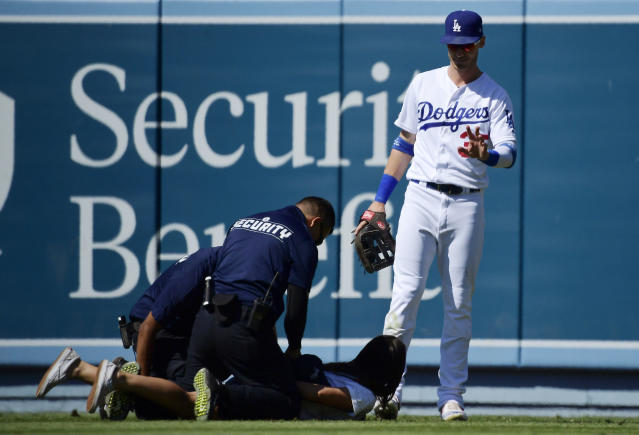 Los Angeles Dodgers right fielder Cody Bellinger, right, waves to a fan that ran out to him as she is handcuffed during the ninth inning of a baseball game against the Colorado Rockies, Sunday, June 23, 2019, in Los Angeles. (AP Photo/Mark J. Terrill)