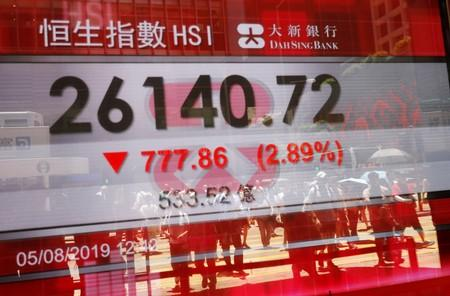FILE PHOTO: The reflections of pedestrians are seen on a screen displaying the Hang Seng stock index in Hong Kong