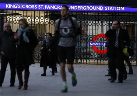 People walk near closed gates during London Underground strikes at Kings Cross underground station in London February 6, 2014. Millions of commuters faced a second day of travel chaos on Thursday due to a 48-hour strike by London Underground workers angry over ticket office closures and job cuts, with no sign of an end to the standoff between unions and rail bosses. REUTERS/Olivia Harris