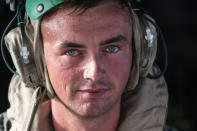 """Sweat beads up U.S. Marine Corps Lance Cpl. Brandon Oldham's face as he waits to take off after loading aid onto a VM-22 Osprey at Toussaint Louverture International Airport, Saturday, Aug. 28, 2021, in Port-au-Prince, Haiti. The VMM-266, """"Fighting Griffins,"""" from Marine Corps Air Station New River, from Jacksonville, N.C., are flying in support of Joint Task Force Haiti after a 7.2 magnitude earthquake on Aug. 22, caused heavy damage to the country. (AP Photo/Alex Brandon)"""