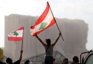 FILE PHOTO: Demonstrators wave Lebanese flags during protests near the site of a blast at Beirut's port area