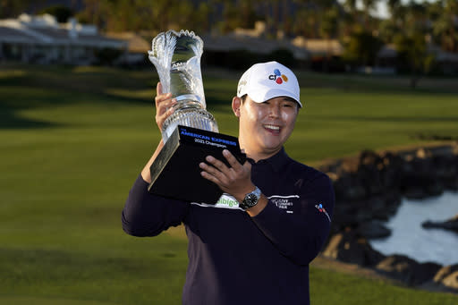 Si Woo Kim holds the winner's trophy at the end of the American Express golf tournament on the Pete Dye Stadium Course at PGA West, Sunday, Jan. 24, 2021, in La Quinta, Calif. (AP Photo/Marcio Jose Sanchez)