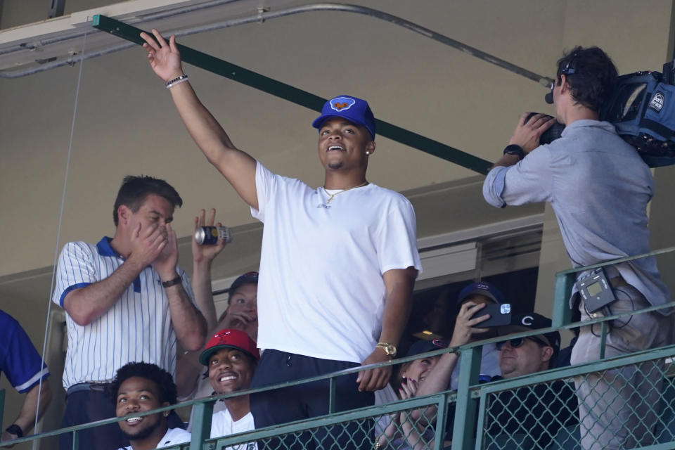 Chicago Bears' first-round draft pick, Ohio State quarterback Justin Fields, acknowledges the applause of the fans at Wrigley Field as he takes in a baseball game between the Chicago Cubs and the St. Louis Cardinals, Friday, June 11, 2021, in Chicago. (AP Photo/Charles Rex Arbogast)