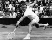 FILE - In this June 29, 1960, file photo, Rod Laver, of Australia, reaches for a shot from Italy's Nicola Pietrangeli during a semifinal at the Wimbledon tennis tournament in London. If Novak Djokovic wins the U.S. Open to complete the first calendar-year Grand Slam in men's tennis in 52 years, Laver will be there to welcome him into a remarkably exclusive club. (AP Photo/File)
