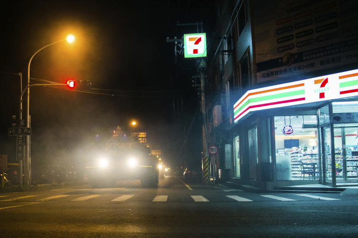 In this photo released by the Military News Agency, a tank rolls past a convenience store as it prepares to take part in the annual Han Kuang live-fire drills in Hualian, eastern Taiwan in the early hours of Tuesday, Sept. 14, 2021. (Military News Agency via AP)