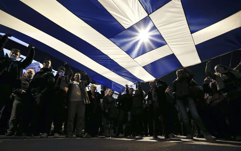 Protesters hold a giant Greek national flag during an anti-austerity and pro-government demonstration in front of the parliament in Athens