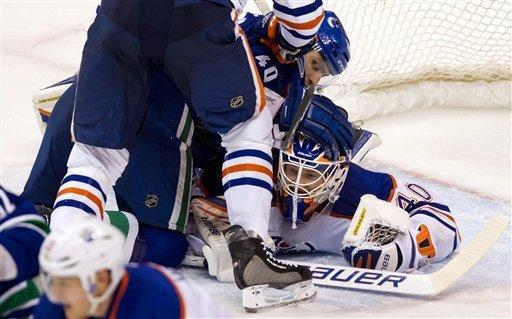Vancouver Canucks' Maxim Lapierre (40) is checked into Edmonton Oilers goalie Devan Dubnyk by Ryan Whitney during the second period of an NHL hockey game in Vancouver, British Columbia, on Tuesday, Jan. 24, 2012. (AP Photo/The Canadian Press, Darryl Dyck)