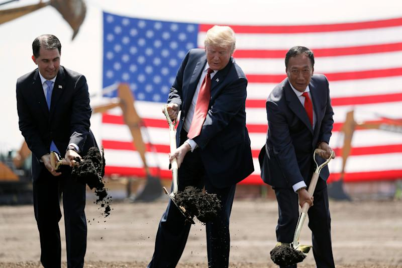 FILE - In this June 28, 2018, file photo, President Donald Trump, center, Wisconsin Gov. Scott Walker, left, and Foxconn Chairman Terry Gou, right, participate in a groundbreaking event for the new Foxconn facility in Mt. Pleasant, Wis. Walker is leaving a fundamentally altered Wisconsin after eight years as governor on Monday, Jan. 7, 2019.(AP Photo/Evan Vucci, File)