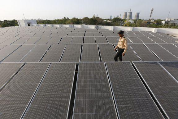 An Indian security guard walks amid a rooftop solar plant in Gandhinagar, India.