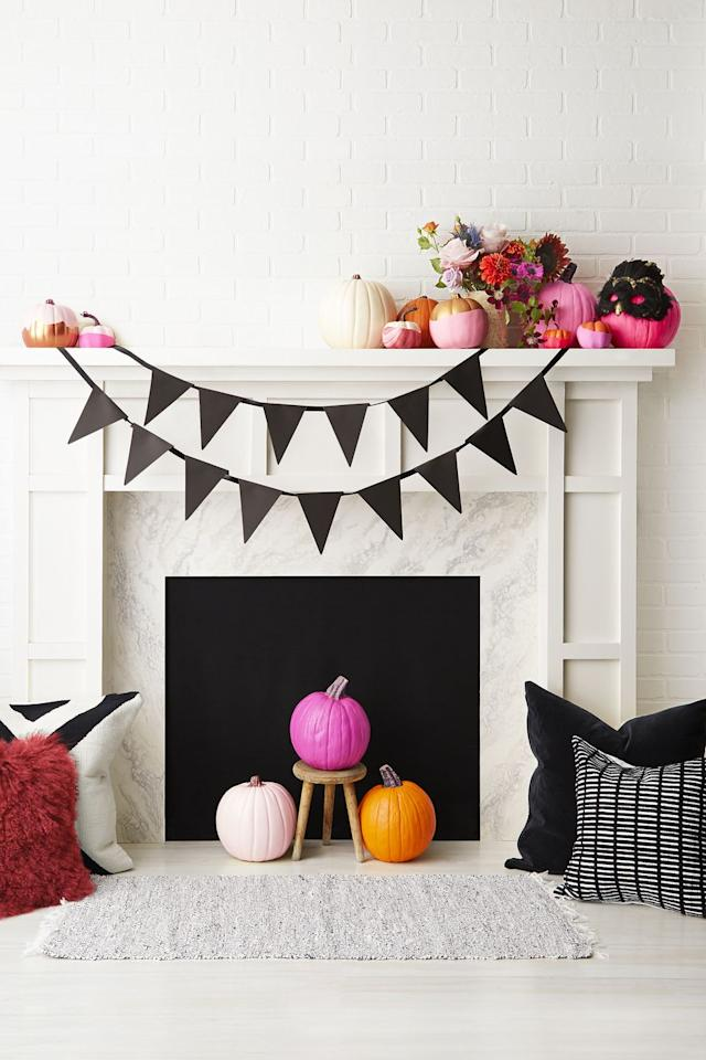 """<p>Think beyond traditional Halloween decor by styling your mantel with an eye-popping mix of brightly colored pumpkins, fresh blooms, and fun accessories. Spray paint pumpkins in gold or pink, then for some, snip the top off a fresh, new balloon and wrap it around the lower part of the gourd. </p><p><strong>RELATED:</strong> <a href=""""https://www.goodhousekeeping.com/holidays/halloween-ideas/g1714/no-carve-pumpkin-decorating/"""" target=""""_blank"""">60+ No-Carve Pumpkin Decorating Ideas</a></p>"""