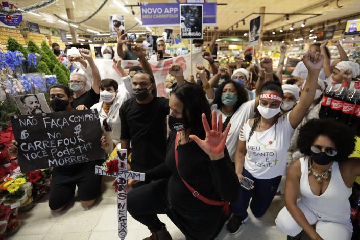 Activists including members of Black Lives Matter demonstrate against the murder of Black man João Alberto Silveira Freitas at a different Carrefour supermarket the night before, on Brazil's National Black Consciousness Day in Brasilia, Brazil, Friday, Nov. 20, 2020. Freitas died after being beaten by supermarket security guards in the southern Brazilian city of Porto Alegre, sparking outrage as videos of the incident circulated on social media. (AP Photo/Eraldo Peres)