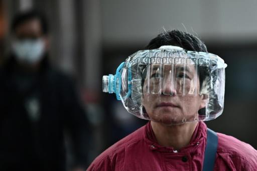 A person wears a plastic water bottle in Hong Kong as a preventative measure as the coraonavirus causes panic around the world