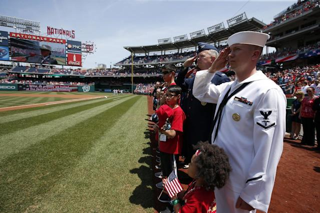 U.S. Navy Hospitalman Third Class Johnathan Loper, right, and others salute during the National Anthem before a baseball game between the Washington Nationals and the Miami Marlins at Nationals Park, on Memorial Day, Monday, May 26, 2014, in Washington. (AP Photo/Alex Brandon)