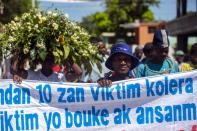 """Cholera survivors carry the Creole message: """"10 years, victims of cholera are tired"""" as they march to the former UN base in Mirebalais, Haiti, Monday, Oct. 19, 2020. Ten years after a cholera epidemic swept through Haiti and killed thousands, families of victims still struggle financially and await compensation from the United Nations as many continue to drink from and bathe in a river that became ground zero for the waterborne disease. (AP Photo/Dieu Nalio Chery)"""