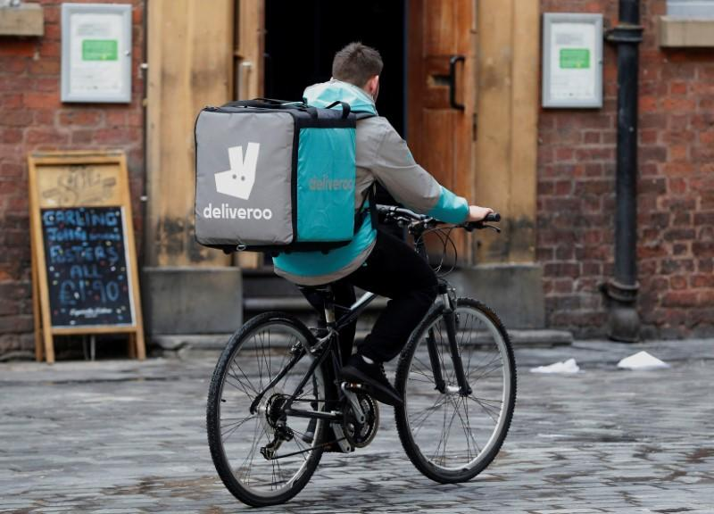 A deliveroo worker cycles along a pedestrianised road in Liverpool