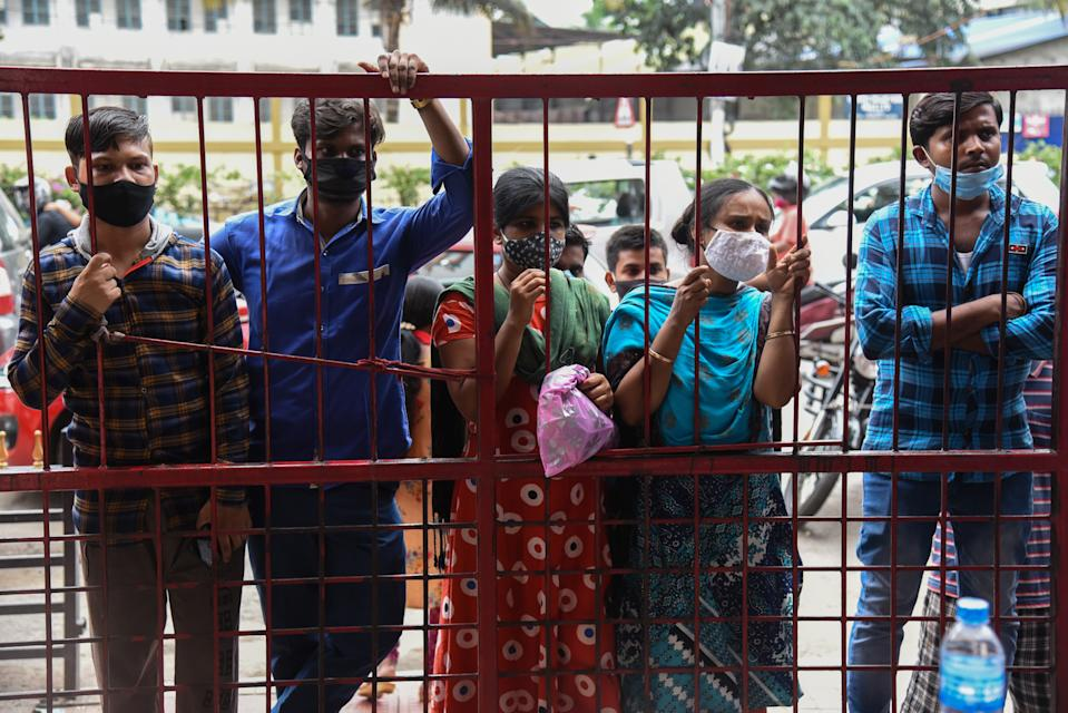 People waiting outside a gate to receive a dose of COVID-19 coronavirus vaccine at a vaccination centre in Guwahati, Assam, India on Saturday, July 3, 2021.  (Photo by David Talukdar/NurPhoto via Getty Images)