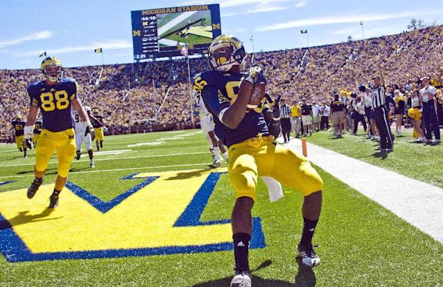Michigan tight end Jake Butt, left, celebrates a touchdown by wide receiver Jehu Chesson, center, in the third quarter of an NCAA college football game against Akron in Ann Arbor, Mich., Saturday, Sept. 14, 2013. Michigan won 28-24. (AP Photo/Tony Ding)