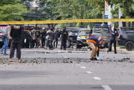 Police officers inspect the area near a church where an explosion went off in Makassar, South Sulawesi, Indonesia, Sunday, March 28, 2021. A suicide bomber blew himself up outside a packed Roman Catholic cathedral on Indonesia's Sulawesi island during a Palm Sunday Mass, wounding a number of people, police said. (AP Photo/Masyudi S. Firmansyah)