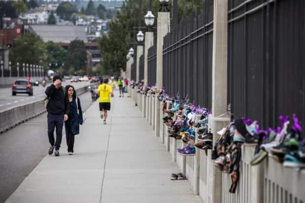 People walk past pairs of shoes hung on the Burrard Street Bridge representing a life lost to a drug overdose on International Overdose Awareness Day, Aug. 31, 2020.  (Ben Nelms/CBC - image credit)