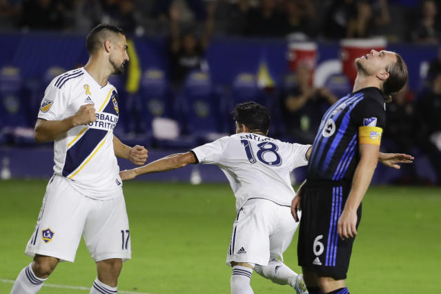 LA Galaxy midfielder Uriel Antuna (18), celebrates after scoring, next to Sebastian Lletget, left, as Montreal Impact midfielder Samuel Piette, right, reacts during the second half of an MLS soccer match in Carson, Calif., Saturday, Sept. 21, 2019. (AP Photo/Chris Carlson)