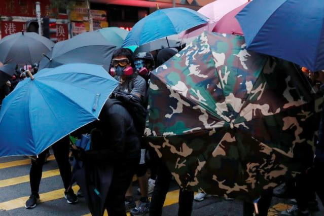 Anti-government protesters hold umbrellas as they march during a demonstration on the New Year's Day to call for better governance and democratic reforms in Hong Kong