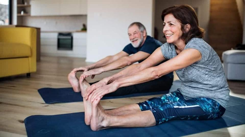 A happy senior couple indoors at home, doing exercise on the floor.