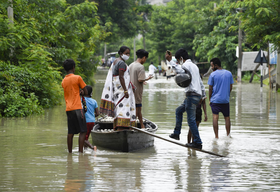 Villager uses a country boat to move across a flooded locality in Kamrup district of Assam, in India on 14 July 2020. (Photo by David Talukdar/NurPhoto via Getty Images)