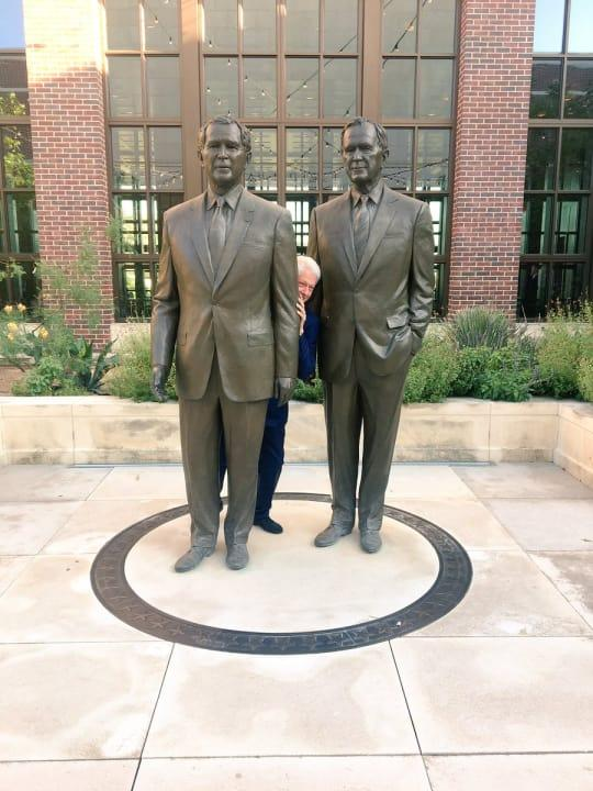 Clinton peeks from behind a statue of former presidents George H.W. Bush and George W. Bush in what many saw as a thinly veiled reference to former Trump White House press secretary Sean Spicer literally hiding in the bushes to avoid reporters.