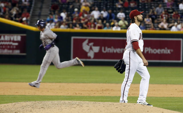 Arizona Diamondbacks' Mike Bolsinger, right, looks away as Colorado Rockies' Troy Tulowitzki (2) rounds the bases after hitting a two-run home run during the sixth inning of a baseball game on Tuesday, April 29, 2014, in Phoenix. (AP Photo/Ross D. Franklin)