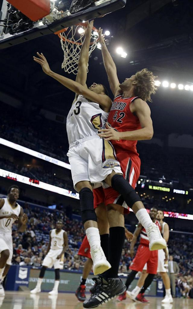 New Orleans Pelicans forward Anthony Davis (23) goes to the basket as Portland Trail Blazers center Robin Lopez (42) tries to block in the first half of an NBA basketball game in New Orleans, Monday, Dec. 30, 2013. (AP Photo/Gerald Herbert)