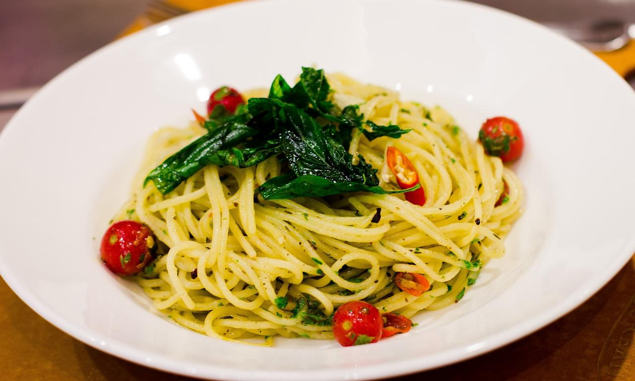 <p>Ingredients<br /> 2 tbsp olive oil<br /> 2-3 cloves garlic, sliced<br /> 1 red chilli, sliced<br /> 100 g spaghetti (boiled al dente)<br /> a pinch of mixed herbs<br /> 2-3 cherry tomatoes<br /> salt and pepper to taste<br /> 50 g Parmesan cheese<br /> 1 tbsp pasta water (saved after boiling)<br /> a few sprigs parsley , chopped<br /> Gently heat olive oil in a pan, add garlic and switch off the gas. Let the garlic infuse the oil for a minute. Put the heat back on and add chilli, spaghetti, mixed herbs, cherry tomatoes, salt and pepper, and toss well. Add the grated Parmesan cheese, some pasta water and toss well with fresh parsley. Serve hot. </p>