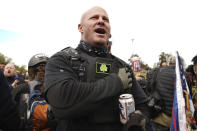 A man does the Pledge of Allegiance as members of the Proud Boys and other right-wing demonstrators rally on Saturday, Sept. 26, 2020, in Portland, Ore. About 200 people gathered in Portland, for a right-wing rally with dozens of them wearing militarized body armor. (AP Photo/Allison Dinner)