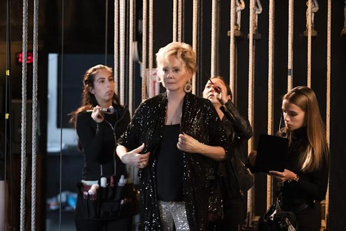 A woman in a black, sparkly jacket getting ready backstage with the help of her hair and makeup team