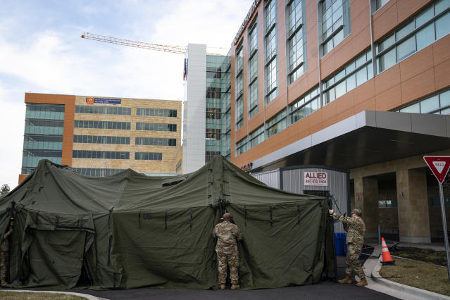 Members of the Maryland Army National Guard set up a triage tent outside the emergency room at Adventist HealthCare White Oak Medical Center in Silver Spring. (Drew Angerer/Getty Images)