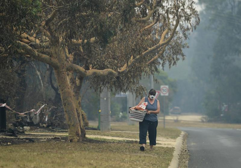 A local walks with smoke mask on in Mallacoota, Victoria. (Photo: Tracey Nearmy / Reuters)