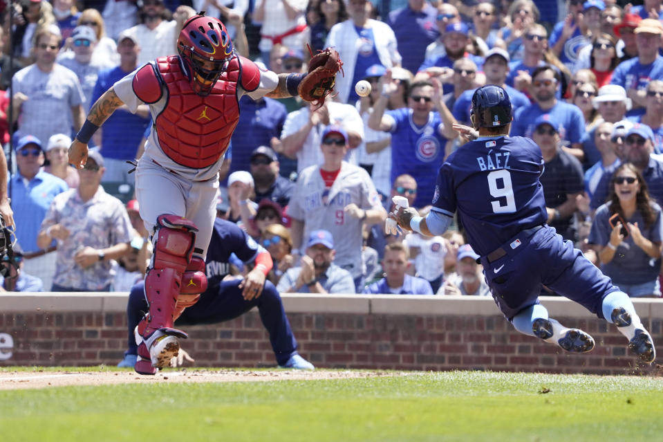 Chicago Cubs'Javier Baez (9) is safe at home plate as St. Louis Cardinals catcher Yadier Molina (4) takes a late throw during the first inning of a baseball game, Friday, July 9, 2021, in Chicago. (AP Photo/David Banks)