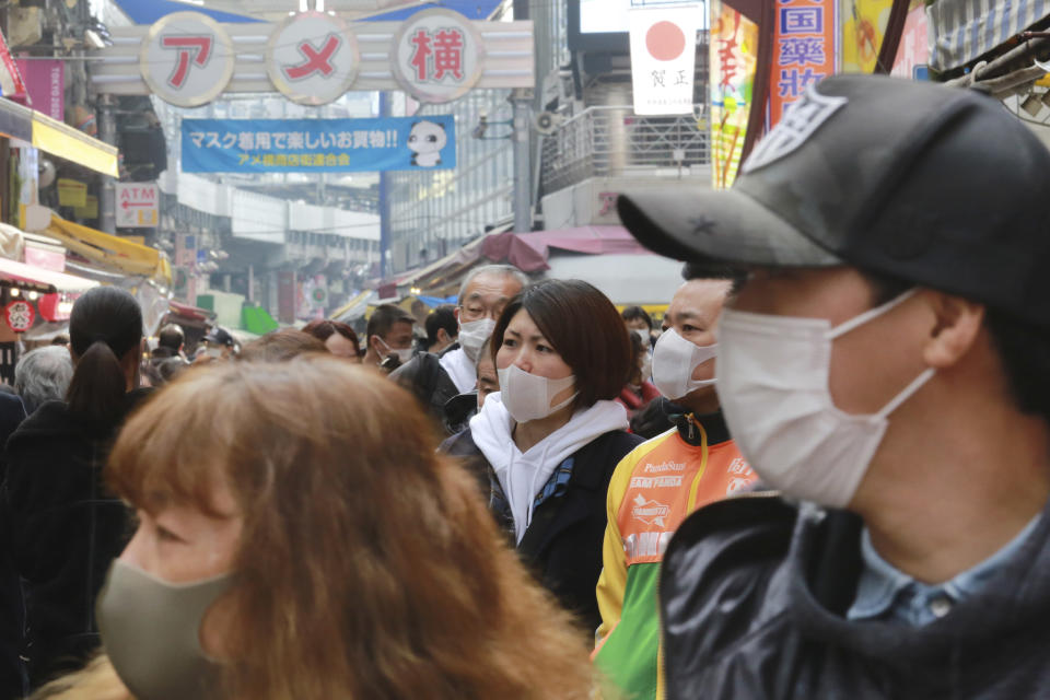 People wearing face masks to protect against the spread of the coronavirus visit the Ameyoko shopping street in Tokyo, Wednesday, Dec. 30, 2020. (AP Photo/Koji Sasahara)