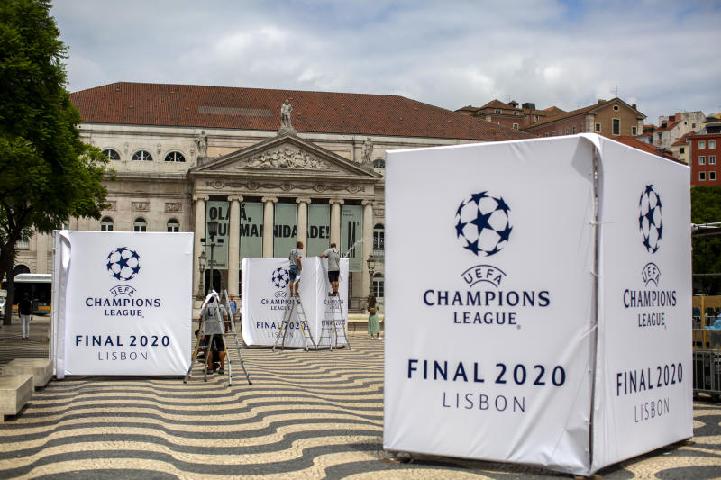 Staff workers set up banners of the UEFA Champions League in downtown Lisbon, Portugal, Wednesday, Aug. 12, 2020. The country has the center stage from Wednesday when eight of Europe's best teams start fighting for the coveted Champions League title amid strict health protocols.(AP Photo/Manu Fernandez)