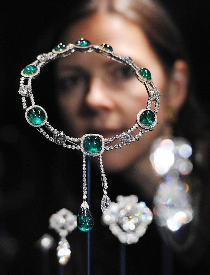 This Thursday June 28, 2012 photo shows curator Caroline de Guitaut, standing behind the Delhi Durbar Necklace and Cullinan Pendant made up of diamonds and emeralds, created for the Delhi Durbar of 1911 and owned by Queen Mary, at a new exhibition at Buckingham Palace, London. The new exhibition at Buckingham Palace shows jewels collected by six monarchs over three centuries to mark the Queen's Diamond jubilee this summer. (AP Photo/Stefan Rousseau/PA Wire) UNITED KINGDOM OUT