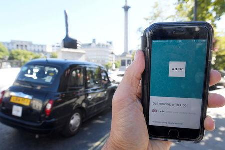 FILE PHOTO: A photo illustration a London taxi passing as the Uber app logo is displayed on a mobile telephone, as it is held up for a posed photograph in central London September 22, 2017. REUTERS/Toby Melville/File Photo
