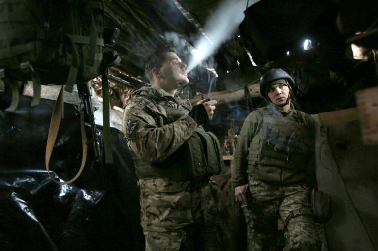Ukrainian soldiers stand in a dugout on the frontline against Russian-backed separatists in the Donetsk region in March 2019