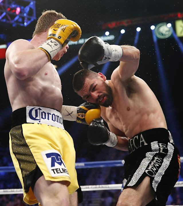 Saul Alvarez of Guadalajara Mexico, left, trades punches with Alfredo Angulo of Mexicali Mexico during their super welterweight boxing match, Saturday, March 8, 2014, at The MGM Grand Garden Arena in Las Vegas. Alvarez won by TKO when the fight was stopped by referee Tony Weeks. (AP Photo/Eric Jamison)