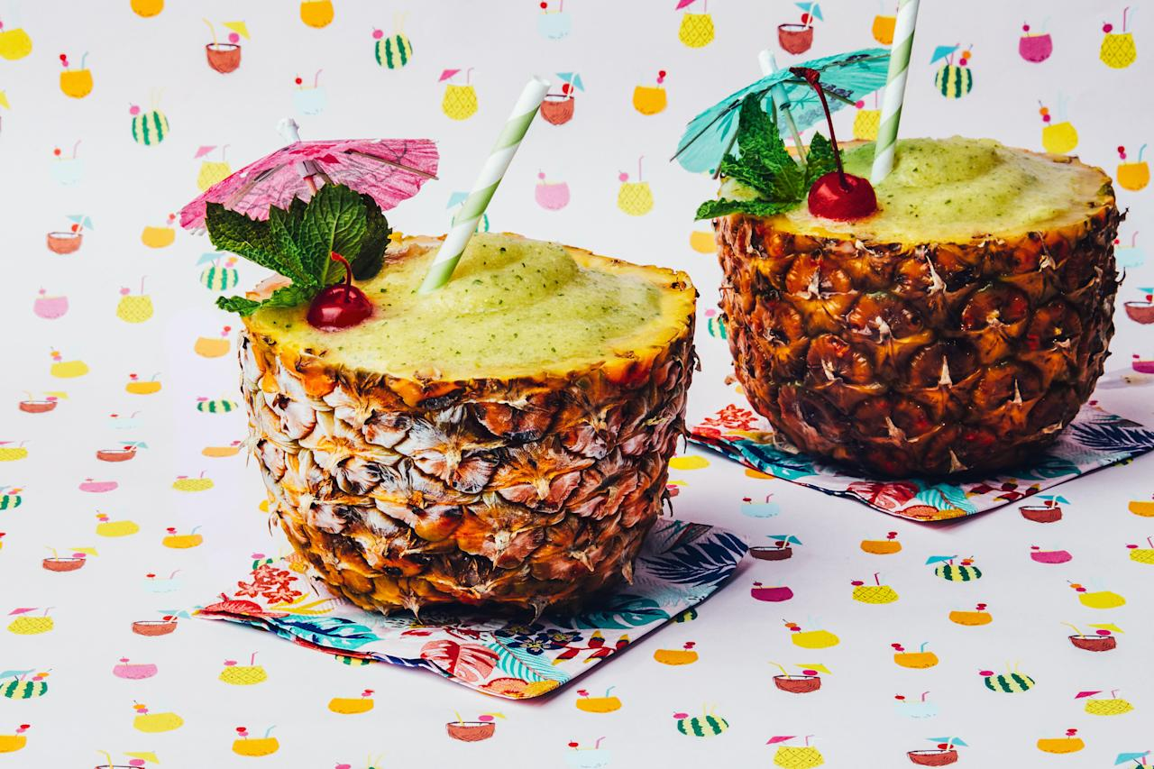 """Pineapple cups make a fun presentation for this frosty poolside cocktail, but random cups from the vacation rental cupboard are fun too. <a href=""""https://www.epicurious.com/recipes/food/views/frozen-pineapple-mojito?mbid=synd_yahoo_rss"""">See recipe.</a>"""